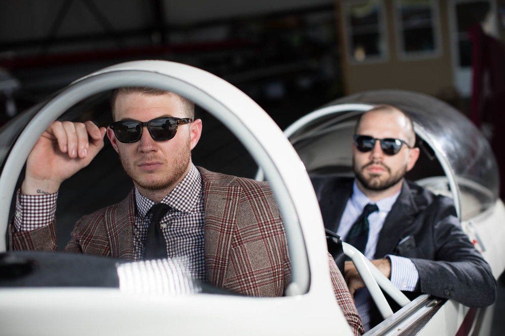 White male models in suits and sunglasses in vintage airplane