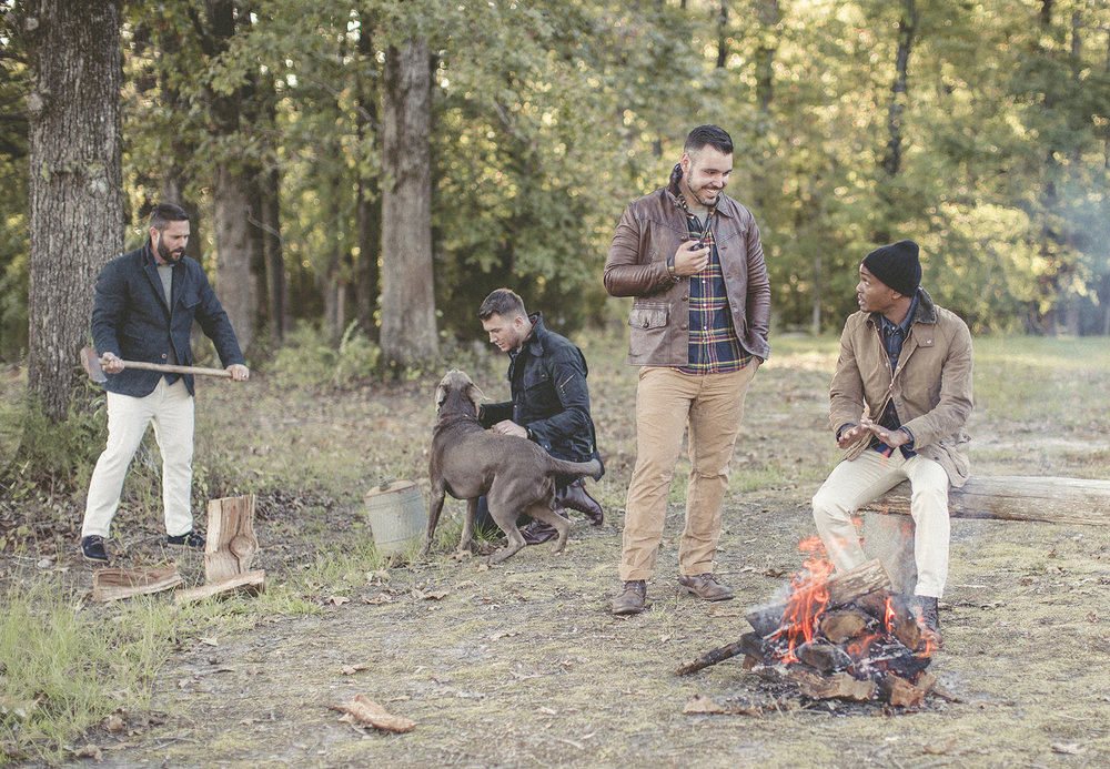 Male models chopping wood with dog and bonfire