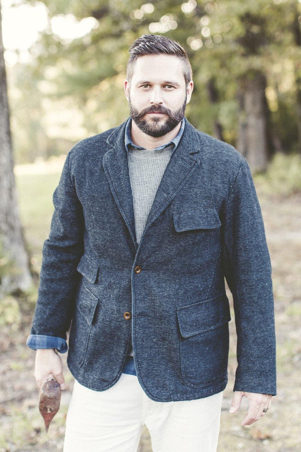 Male outdoorsmen in sport coat with ax
