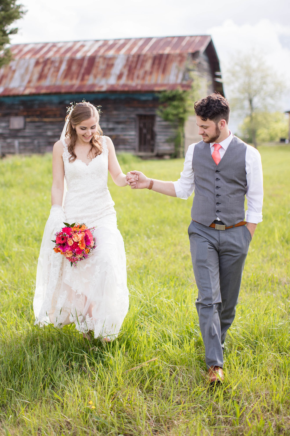 Wedding photography bride and groom first look with bouquet in field