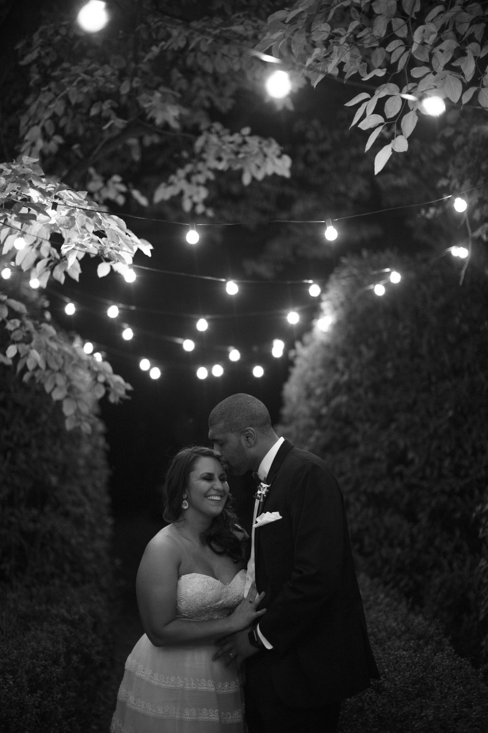 Wedding photography bride and groom string lights first look