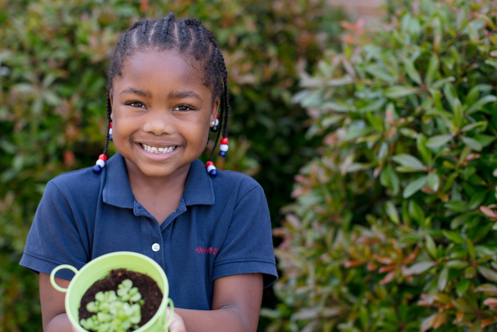 elementary student smiling with plant