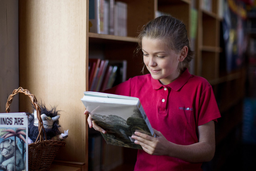 elementary school student reading in library