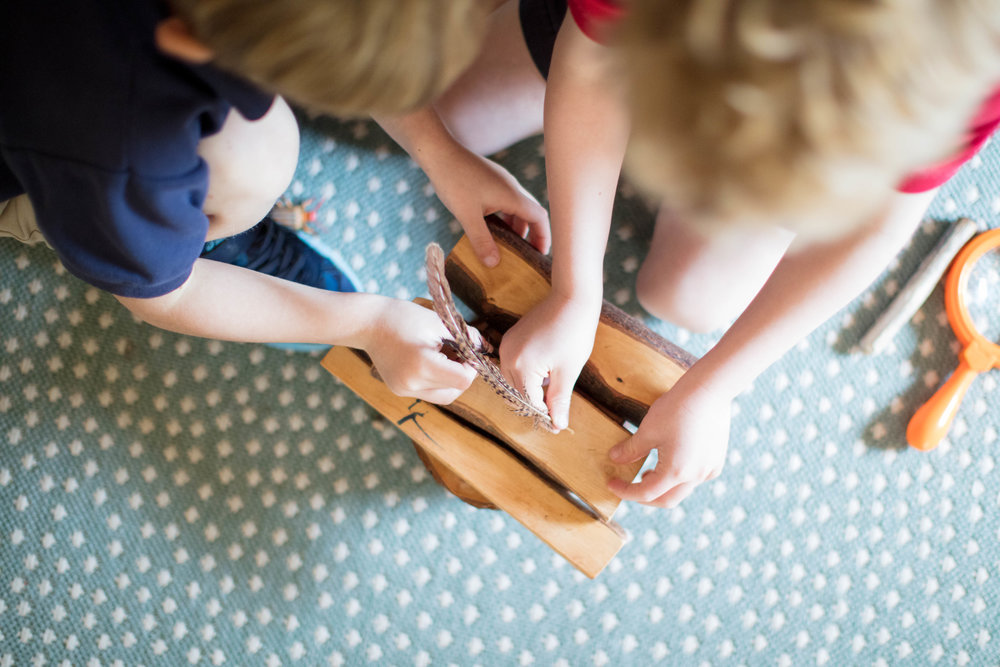 children playing with wood blocks and feather