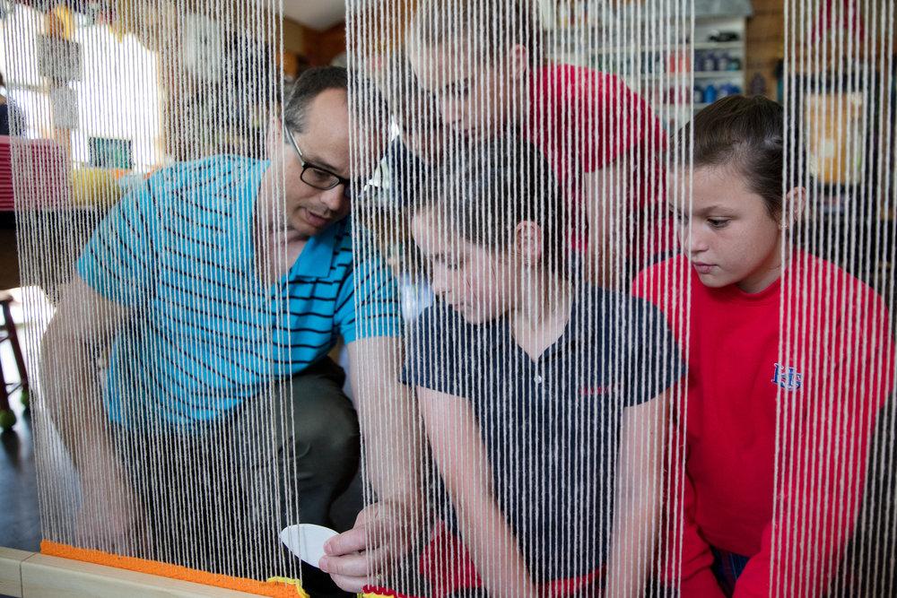 art teacher showing students yarn loom
