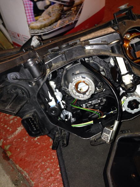 View of back of headlamp with cover and bulb removed. Note metal wiring connector towards bottom right.