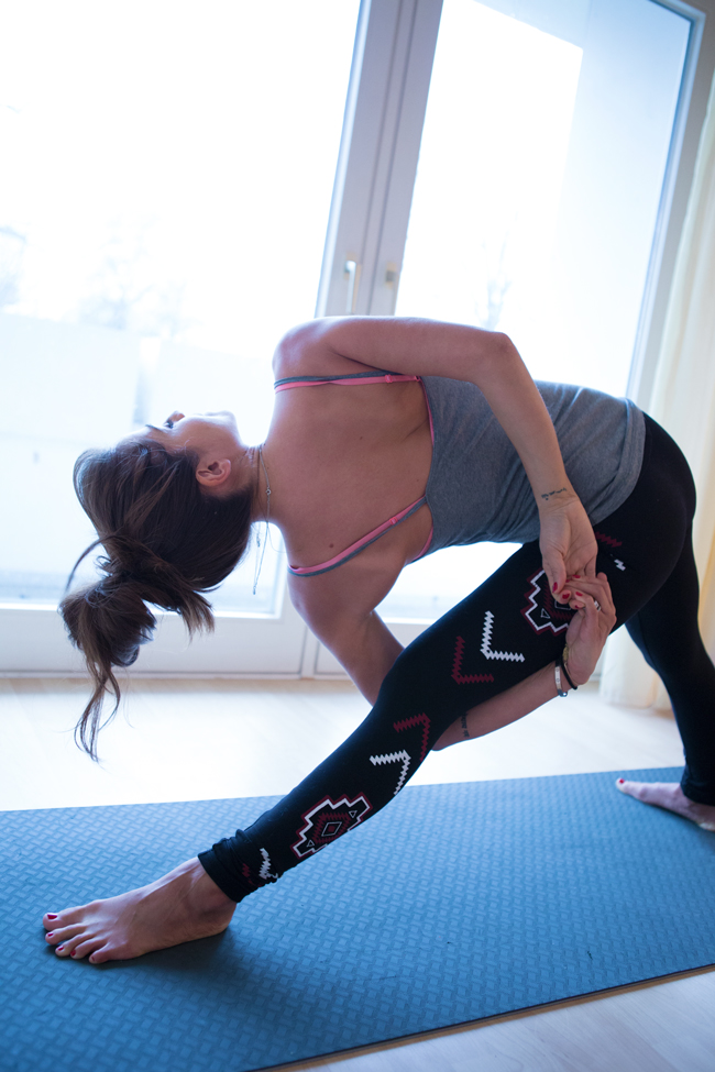 Trikonasana with a bind Wearing: bra, pants (similar), tank.