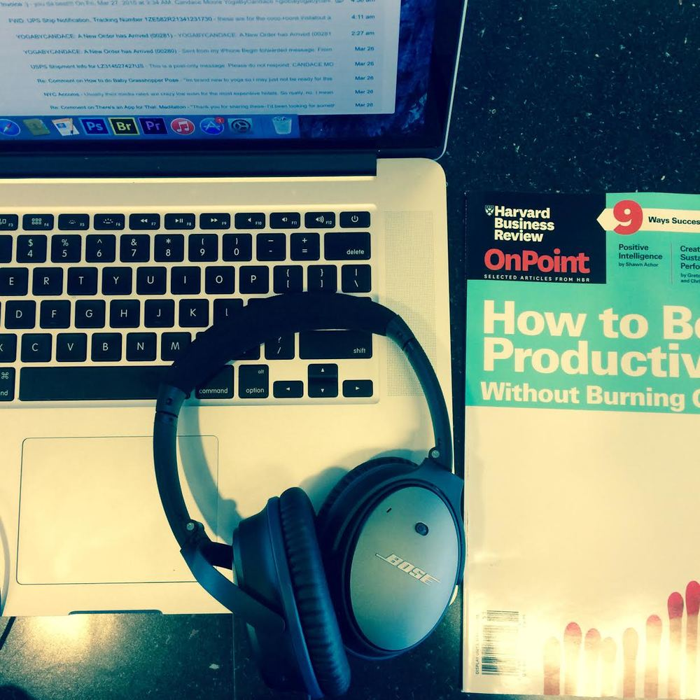 Makeshift workstation with computer, headphones and this Spring's HBR's On Point