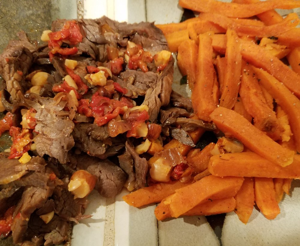 Metabolic Meals grilled grass-fed flank steak with Romesco salsa and sweet potato fries.