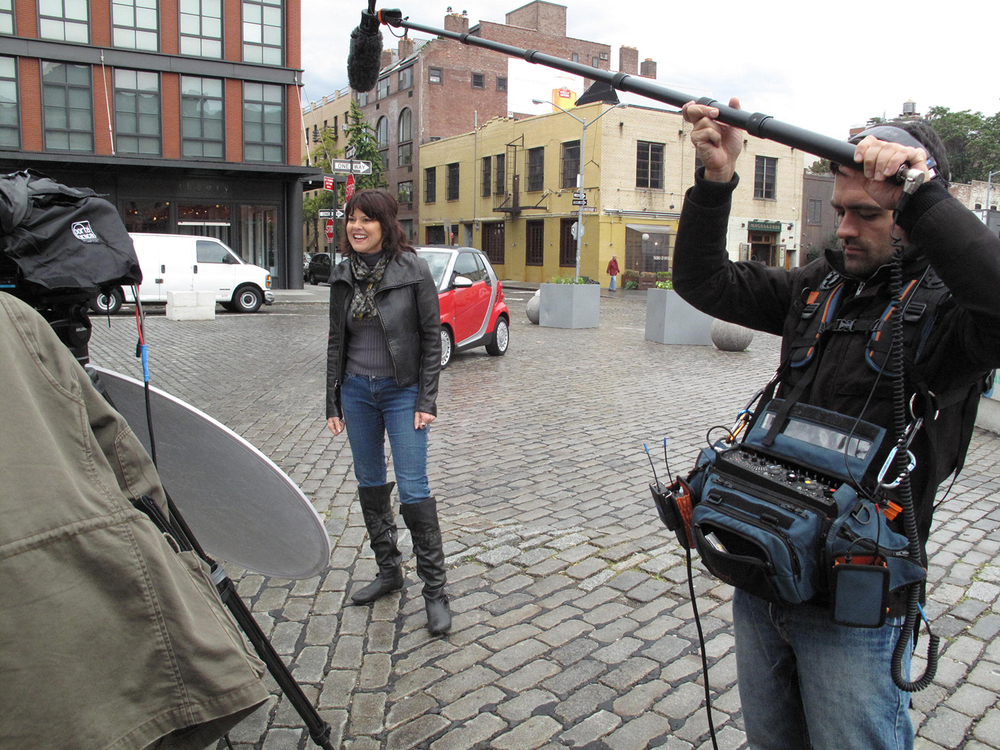 Leslie Hughes and a red Smart Car in the Meatpacking District in NYC.  Rick Lombardo is recording sound.