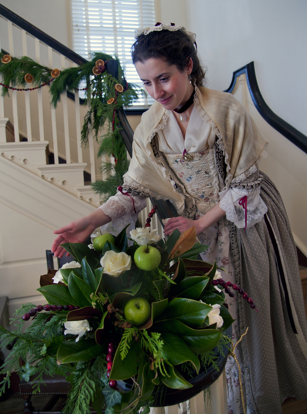 A costumed interpreter prepares to greet visitors by the elegant staircase