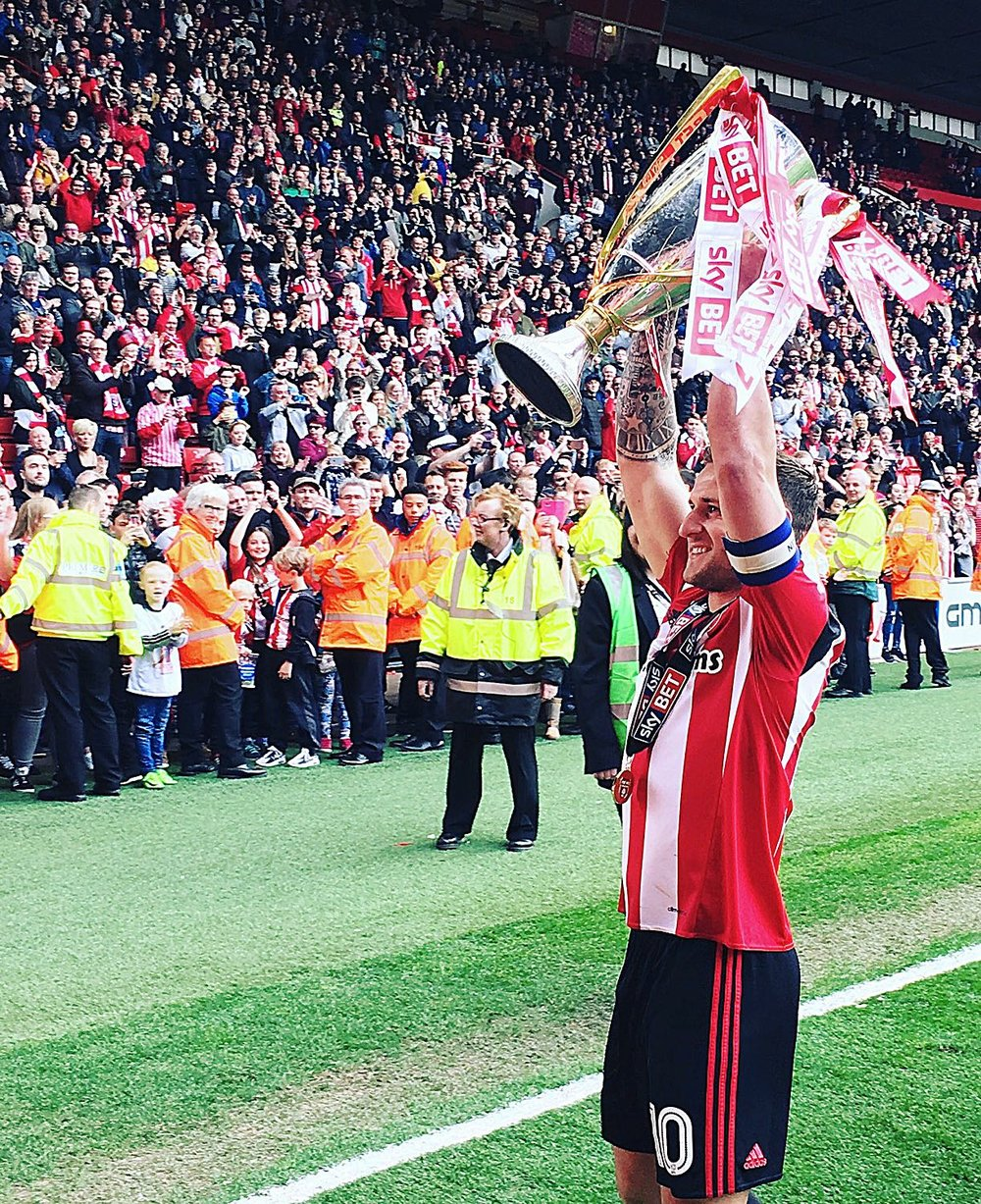 MAN OF THE MOMENT:  BILLY SHARP HOLDS THE LEAGUE ONE TROPHY ALOFT IN FRONT OF FELLOW BLADES