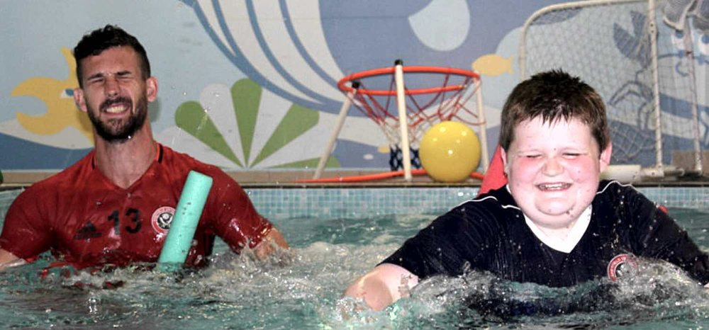 MAKING A DIFFERENCE - United defender Jake Wright and young Blades fan Daniel George-Herbert enjoy a splashing time during a hydrotherapy session for the youngster in Sheffield.