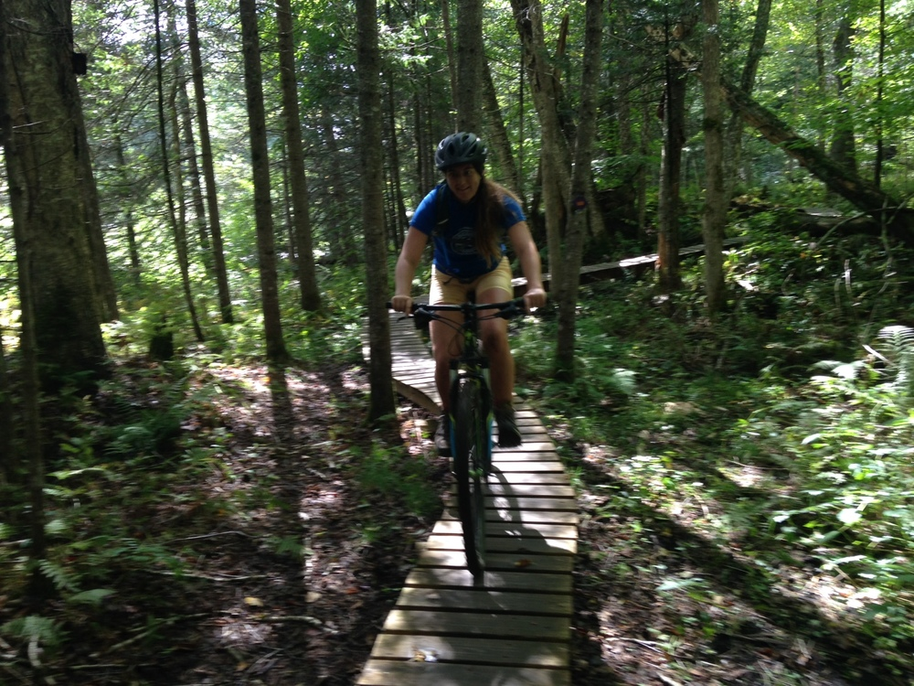 Lilly navigating one of the many technical bridge sections in their trail system.