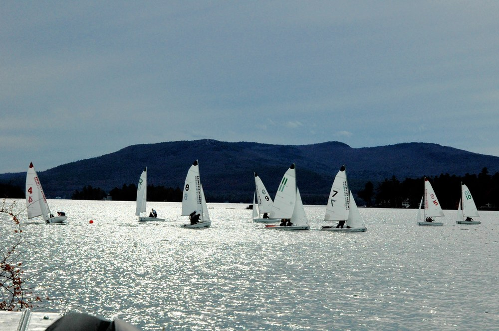 Half the fleet have rounded the leeward mark, visible on left.  In boat #11 Silas and Theresa battle with Brewster team in boat #7 for first place.  Gunstock Mountain in background.