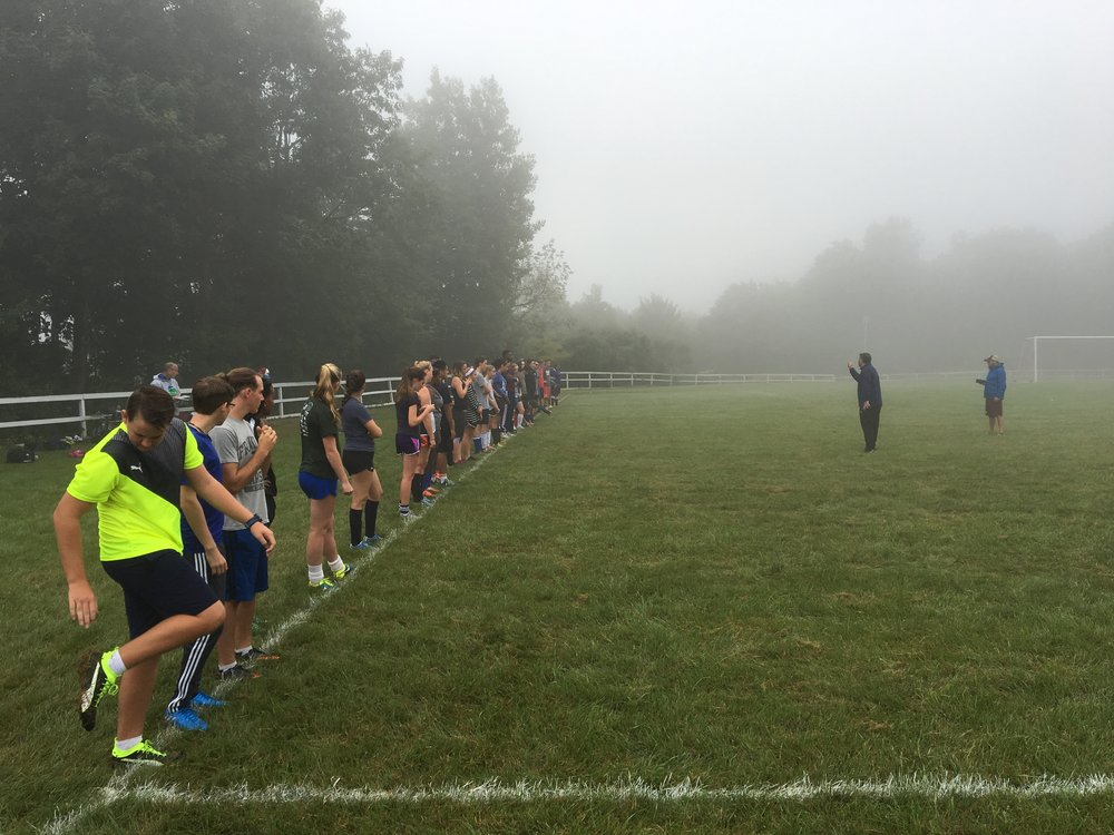 Mount Monadnock is shrouded in mist as Coach McFall leads the squad in a beep fitness test.