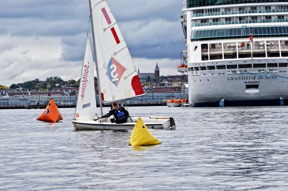 In unusual near glassy-calm Taya and Reed cross the finish line with downtown Portland and a cruise ship looking on from background.