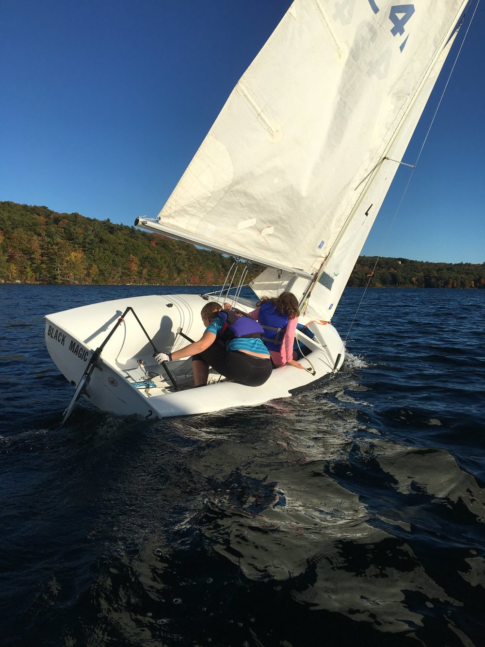 Within easy coaching distance in front of the motorboat, Taya and Rebecca work on a roll tack.