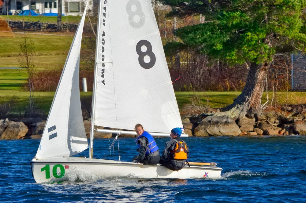Taya showing excellent crew 'head out of the boat' form, calling a layline for driver Silas, Brewster Academy campus in background.