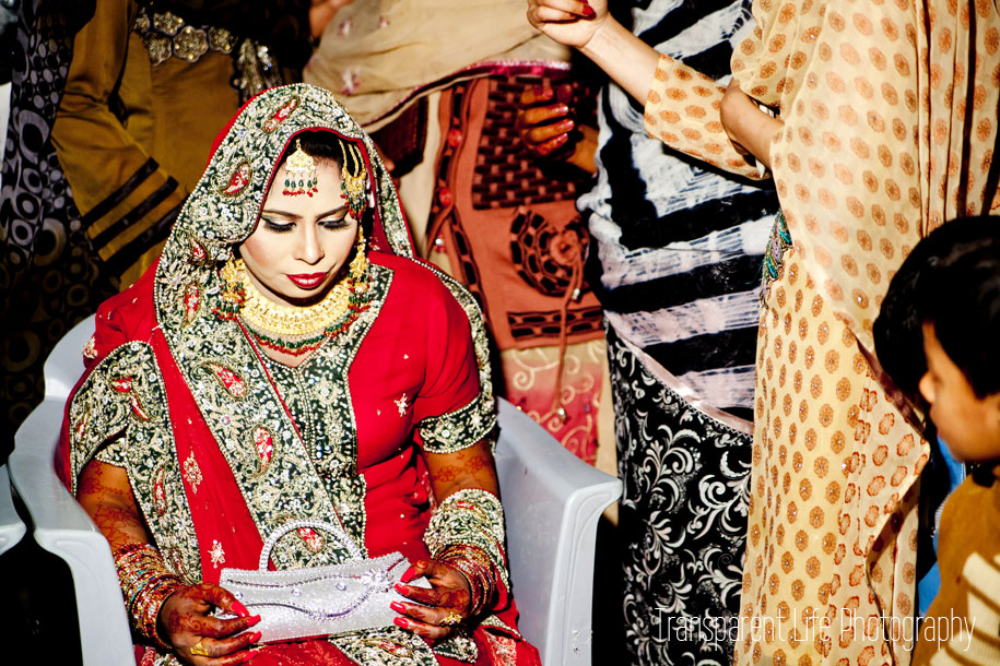 After the ceremony, the bride is dressed up in a traditional wedding dress--the lehenga. It's covered with beading, handiwork and stitching. Also, if you notice, the bride is not smiling--she's supposed to look like that. If she smiles it actually makes her family look bad, like she's happy to leave them. She is supposed to be a shy bride. She did well.
