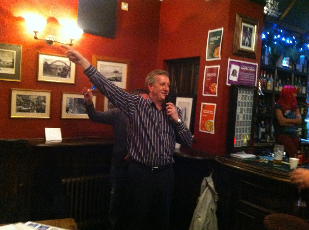 Quiz Master John enjoys a good dart off so much, he's having a Travolta moment!