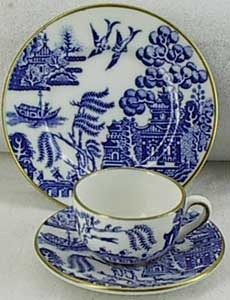 Blue willow cup and saucer, and plate. Note gold trim and birds.