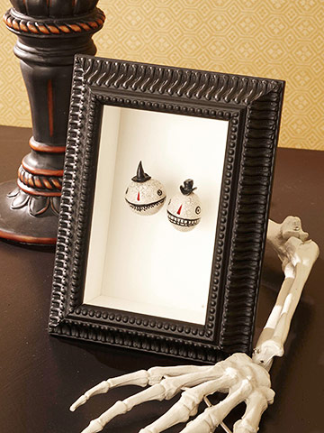 Shadow boxes  work just as well as photos, though are probably more expensive to create.  You can always take a photo of Halloween trinkets and objects like these against a white or black background for the same effect.