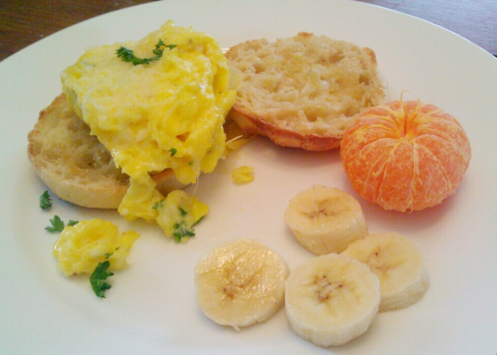 Brunch menu: Perfectly layered, fluffy, scrambled eggs, with English muffins, tangerines, banana slices, and your choice of jelly, jam, marmalade, or preserve.