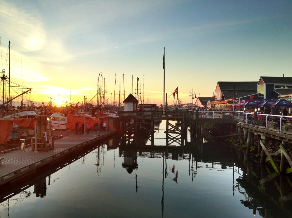 The sun starts to set over the harbour in Steveston.