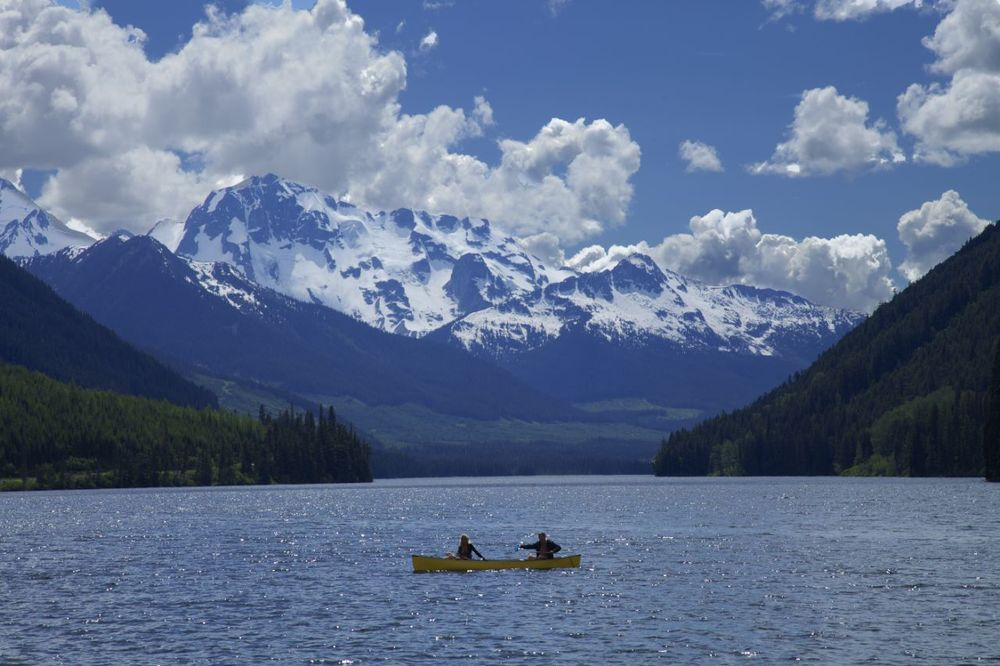 It was a beautiful day, and the canoeists were enjoying their time on the water, with the mountains providing a great backdrop.