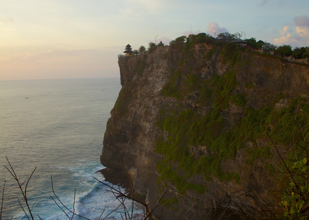 The temple is perched high on a cliff overlooking the ocean. It provides dramatic views, especially at sunset.