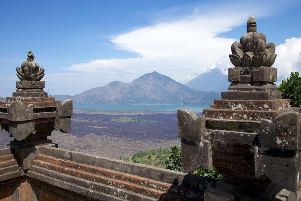 Mount Batur and Lake Batur from the temple. The volcano and the lake provide a stunning backdrop, especially on a clear, blue day.