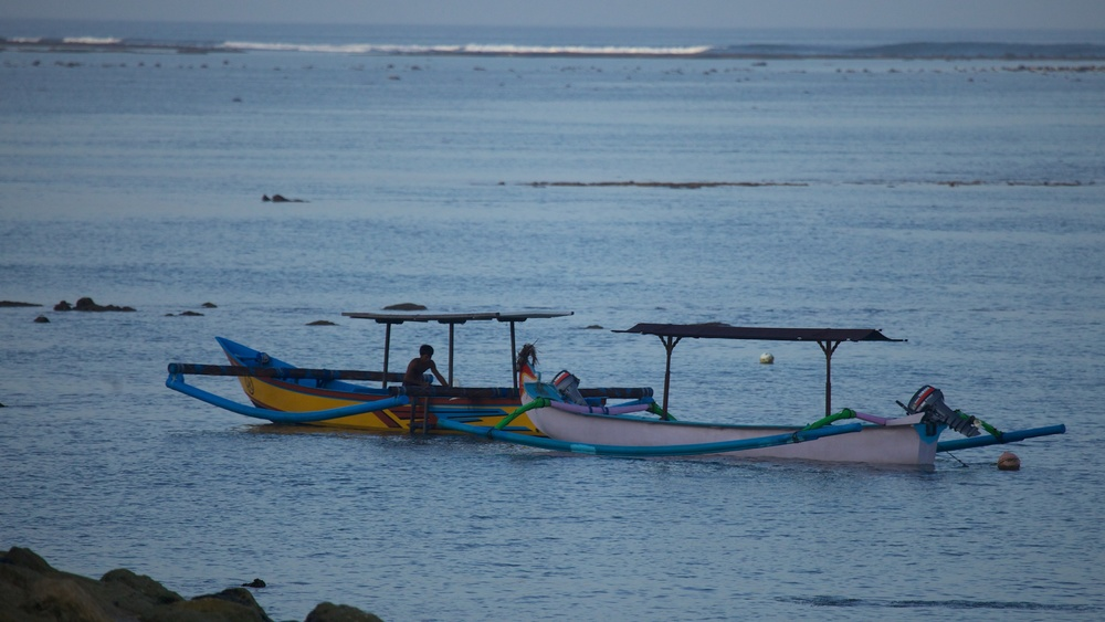 A couple of small boats, anchored just off the beach.