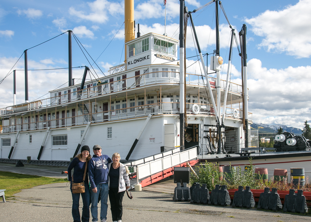 Justine, Dad and Mom in front of the S.S. Klondike on a sunny summer day in Whitehorse.