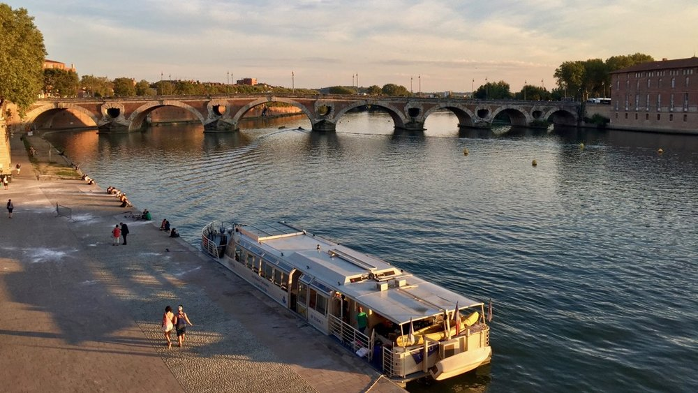A river boat on the River Garonne, in front of the Pont Neuf in downtown Toulouse.