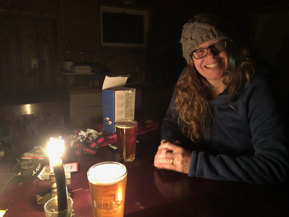 Playing cards and drinking beer by candlelight.