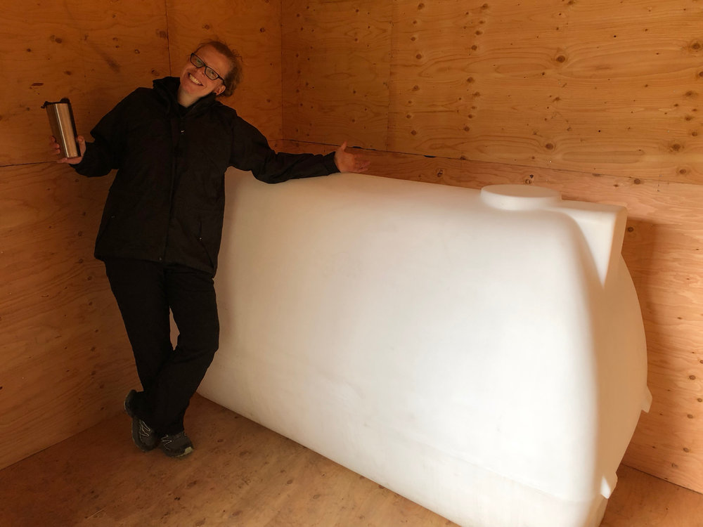 The inside, with Justine posing with our 450 gallon holding tank. The water guy suggested this size, to give the water the ability to settle,a nd to provide some back up for our somewhat slow well. Our neighbour went with 4,000 gallons…