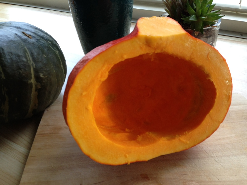 Halved & insides scooped out Red Kuri Squash, ready for the oven.