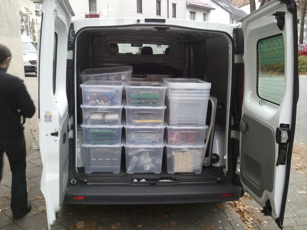 Van is almost full with lot of transparent plastic boxes.