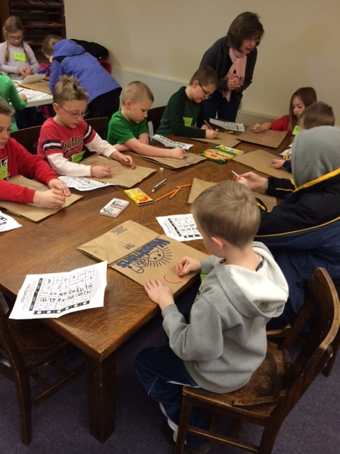 Working on paper bag masks, using a Picasso dice roll game to pick facial features. Photo property of Laura Damon-Moore.