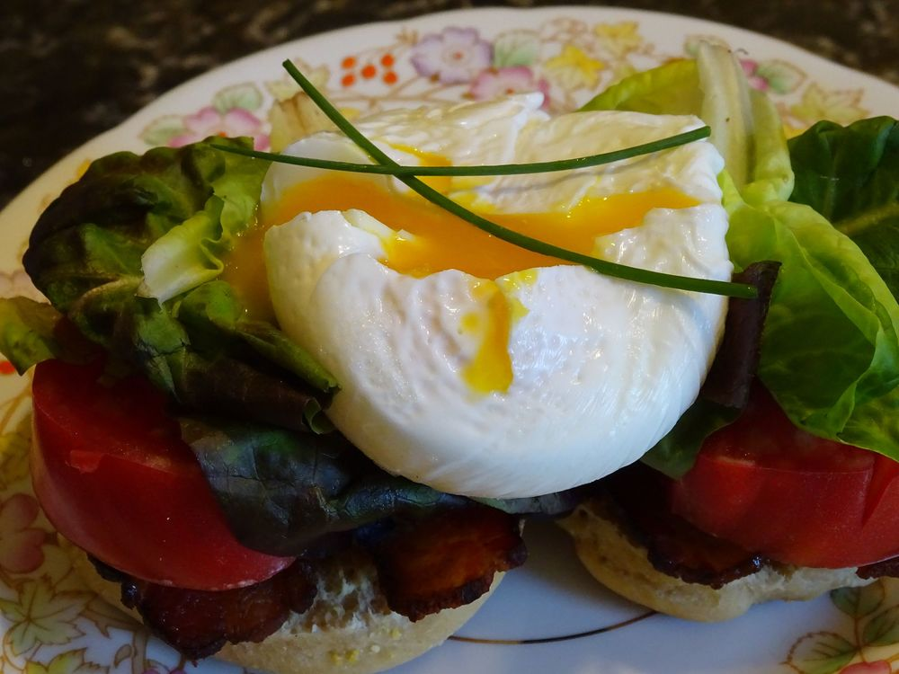 Breakfast BLT - homemade English muffin, bacon, lettuce & tomato, topped with a perfectly poached egg.