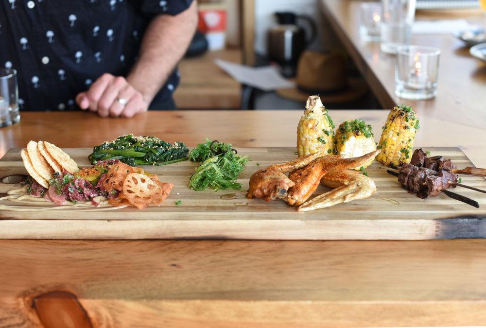 Tochi Land Board - beef tartar, kushiyaki, miso corn, chicken wings, beef heart yakitori & wakame.