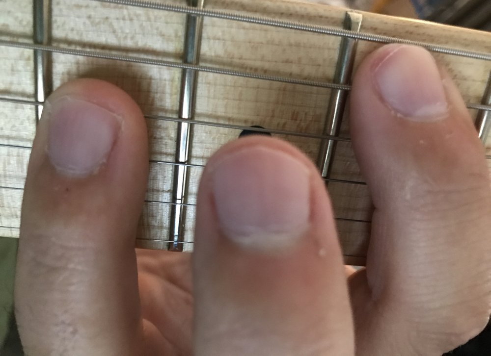 Use the tip of your index finger to mute the low E while playing chords on the A string.