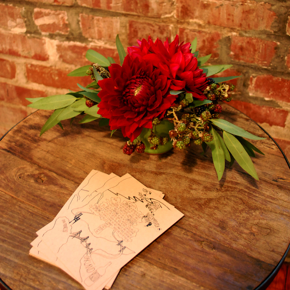 Dahlia's with bay leaves adorn this wood table.