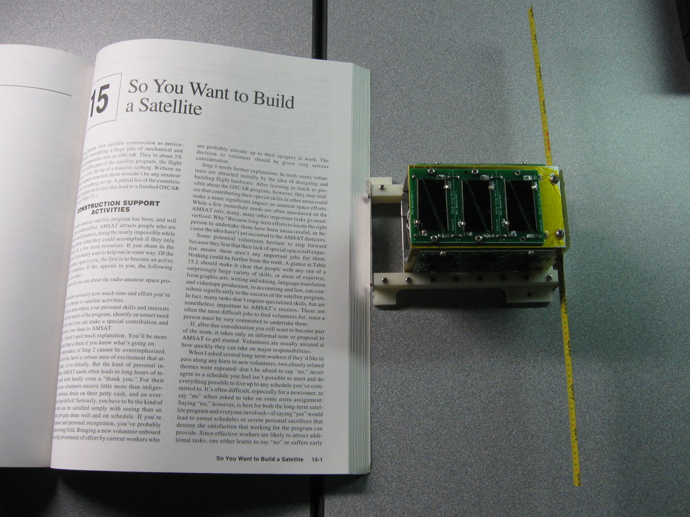 The $50sat PocketQub shown next to an inspirational page for scale. Take a look at the satellite's yellow antennas. Just like the original Oscar, the budget satellite uses a metal tape measure rather than an expensive high-tech antenna. Source: 50dollarsat.info