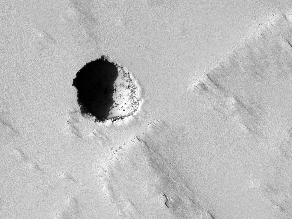 Seventh grade students asked Nasa to take this high-res picture of Mars using the Mars Reconnaissance Orbiter's HiRise camera. It may be a skylight cave - the collapsed roof of a lava tube - and could be a target for future human explorers. Credit: Nasa/JPL/University of Arizona