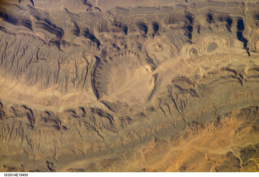 In some cases craters overlap existing geological features like this valley-side impact in Algeria.  ( Source )
