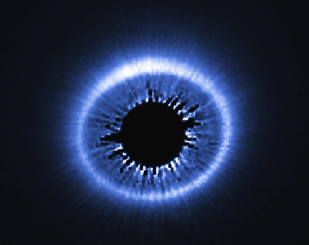 The infrared glow emitted by the disk of dust and debris surrounding a young star (masked in the center) may someday form planets.  Source:  Nasa/Esa/Univ. of Arizona/HST/GO 12228 Team