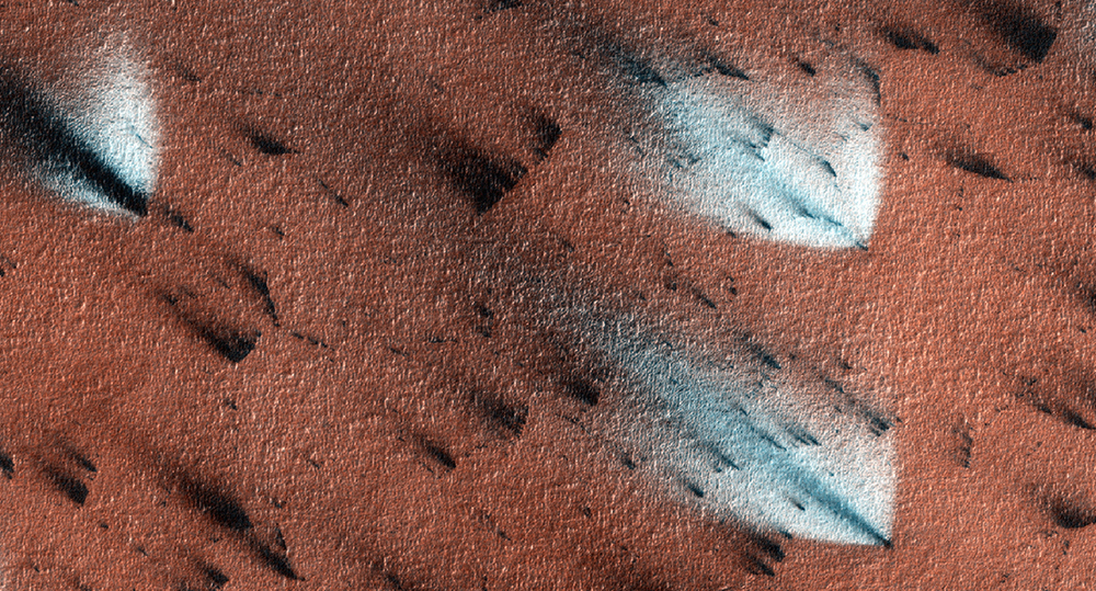 "Carbon dioxide ice blankets Mars during the winter. Dust clouds puff out of the ice during the spring thaw to form these dark ""fans"". Once the ice sublimates away the dust blends into the Martian surface and the fans disappear. Planet Four crowdsources maps of these dust fans to study Martian wind patterns.  Credit:  Nasa/JPL-Caltech/University of Arizona"