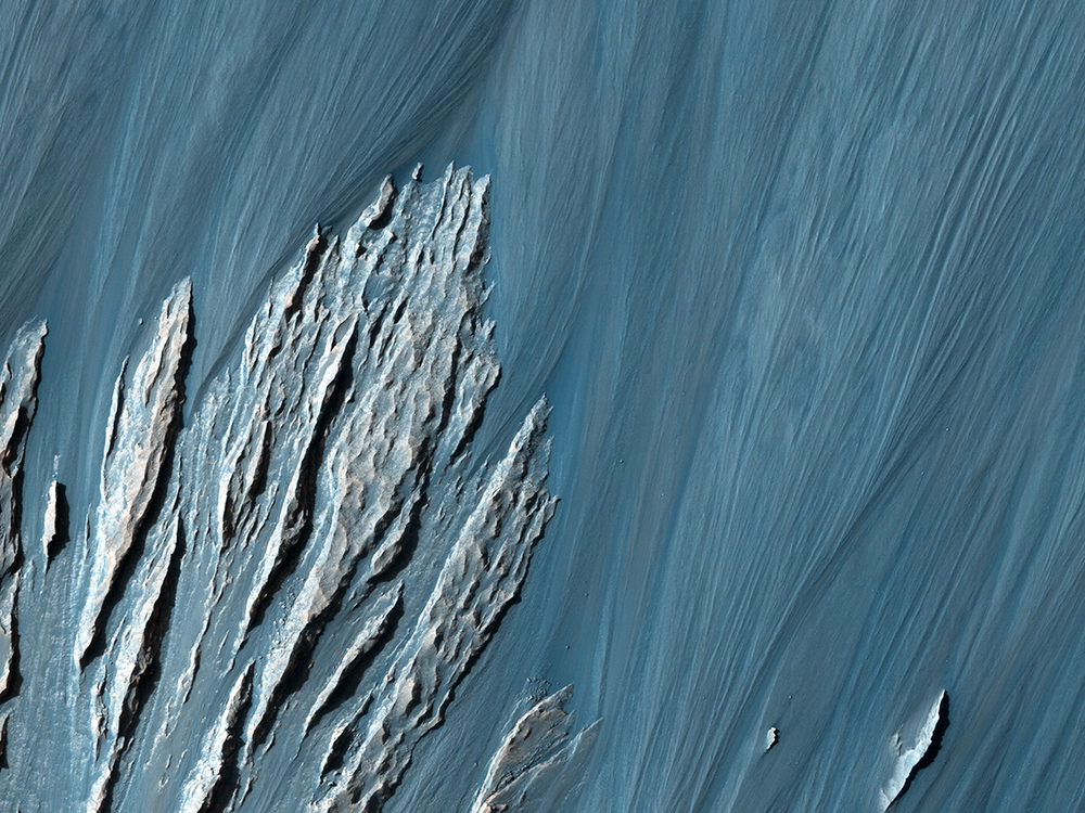 Landslides along the cliffs of Hebes Chasma uncovered rock layers which scientists can use to study Mars' geological history.  Credit: Nasa/JPL-Caltech/University of Arizona